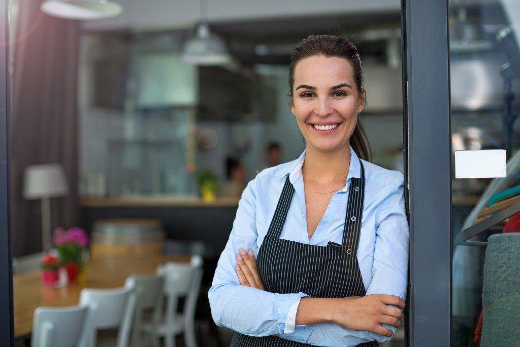 Business owner standing at the door of restaurant