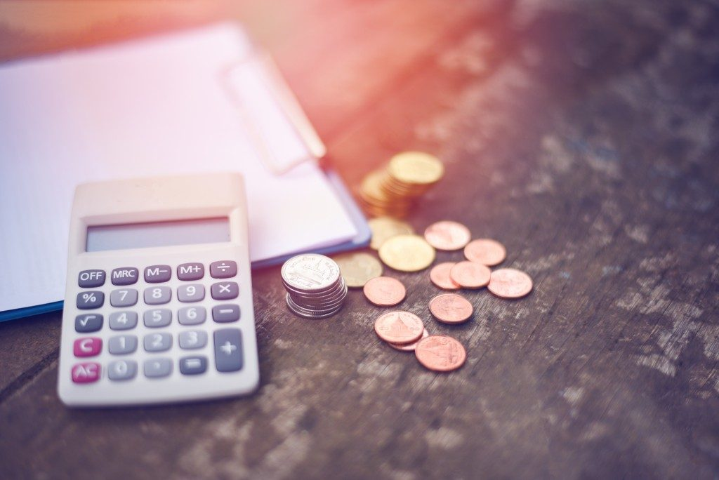 Calculator, paper, and coins on the table