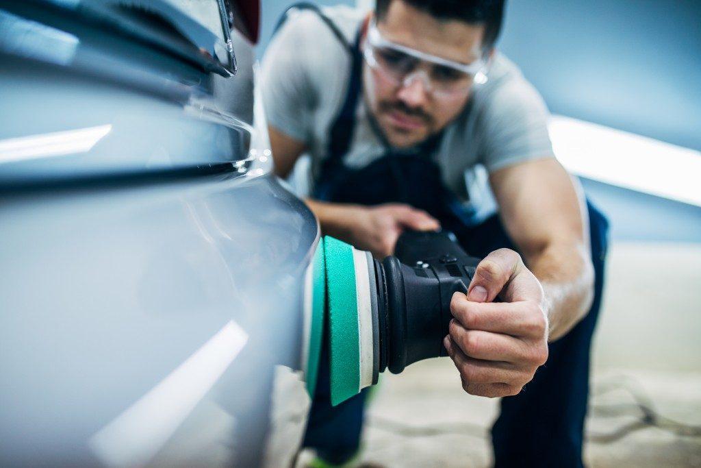 Worker in sealed eyewear cleaning a car