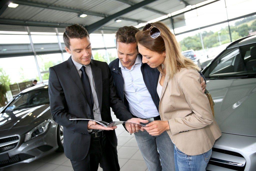 Salesman presenting brochure to clients