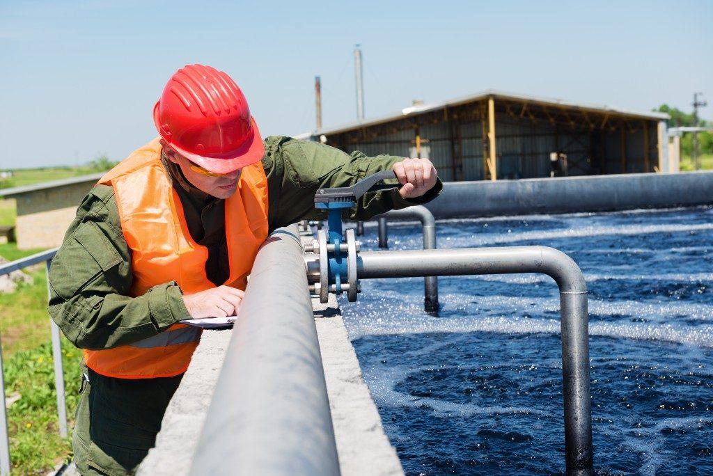 man inspecting a sewage system