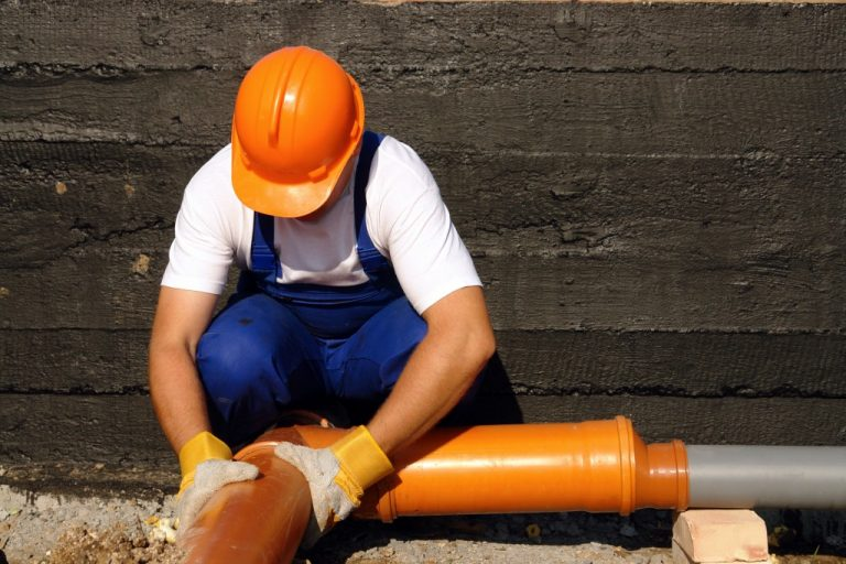 man fixing a sewer pipe