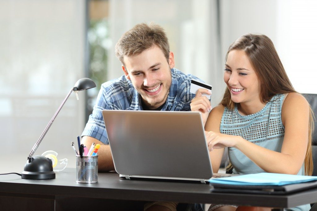 Couple buying online together with a laptop on a desk at home