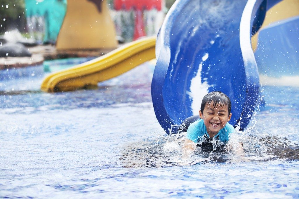 Cute asian boy having fun splashing into pool after going down water slide