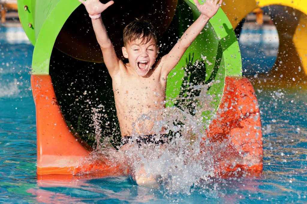 kid coming out from the slide in a water park
