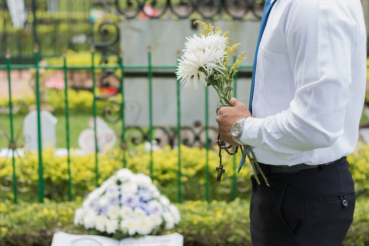 man holding flowers at cemetory